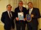 Il presidente del Rotary Santhia-Crescentino Agostino Pino (al centro), il past presidente Livio Autino e il presidente di Ipsia Vercelli espongono la targa che sarà affissa alla Estrela do Mar